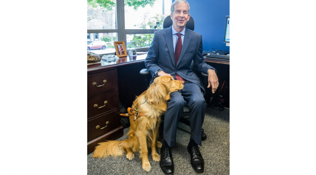 Mike May with guide dog Jonnie in his office
